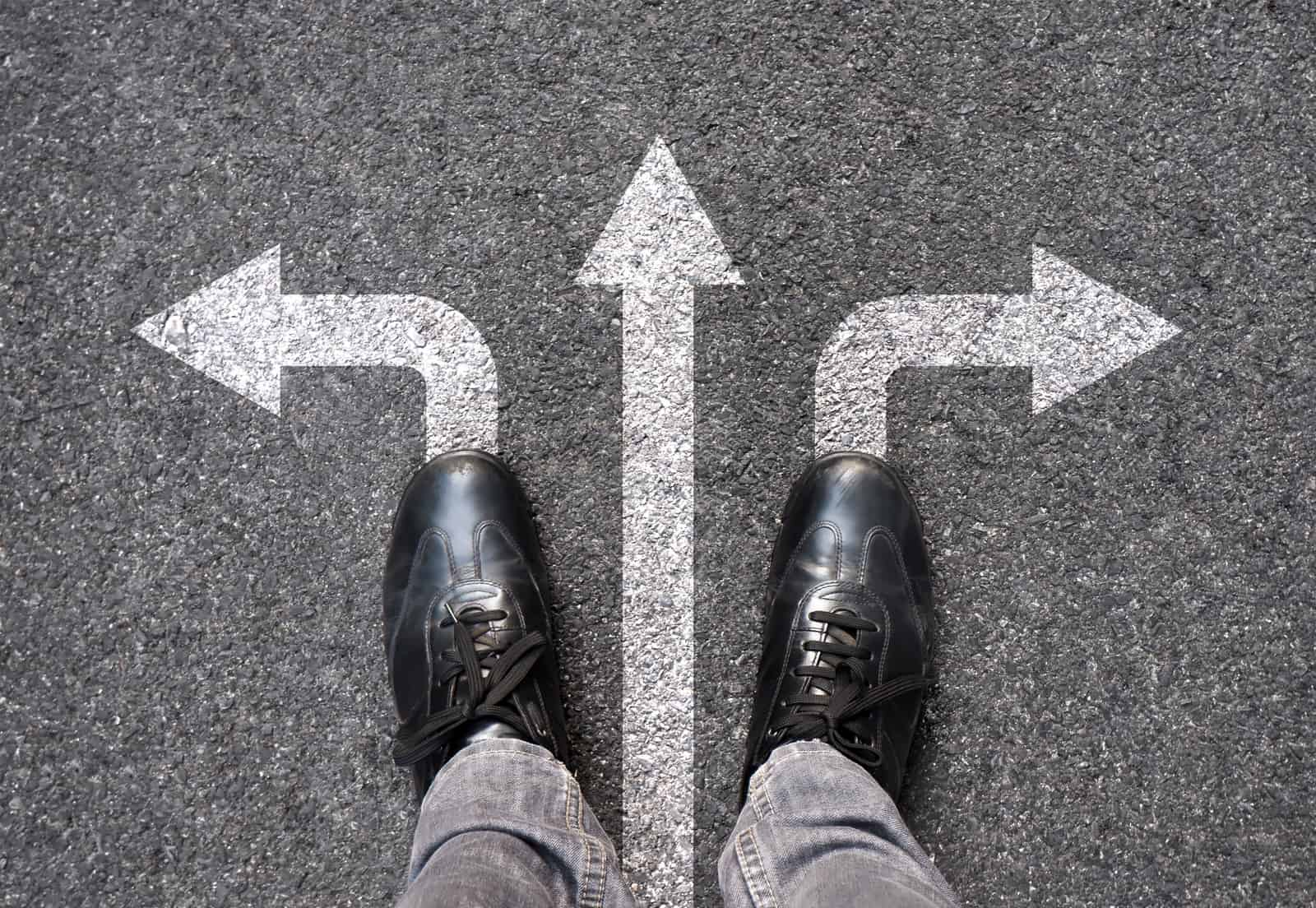 Feet and arrows on road background. Selfie feet above. Businessman standing on pathway with three direction arrows choice or move forward. Top view of business shoes walking. Motivation and growth.
