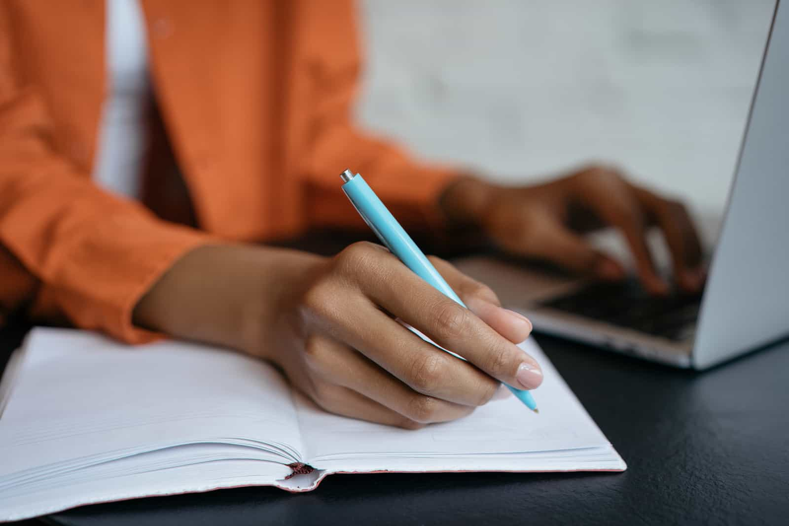 Close-up shot of student hand holding pen and writing in notebook, working at home. E-learning